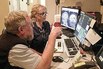Dr. Stephen Dager and Mindy Dixon look over brain scans.