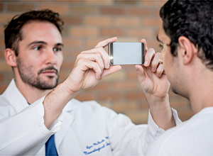 picture of a physician using a smartphone to take a picture of a man