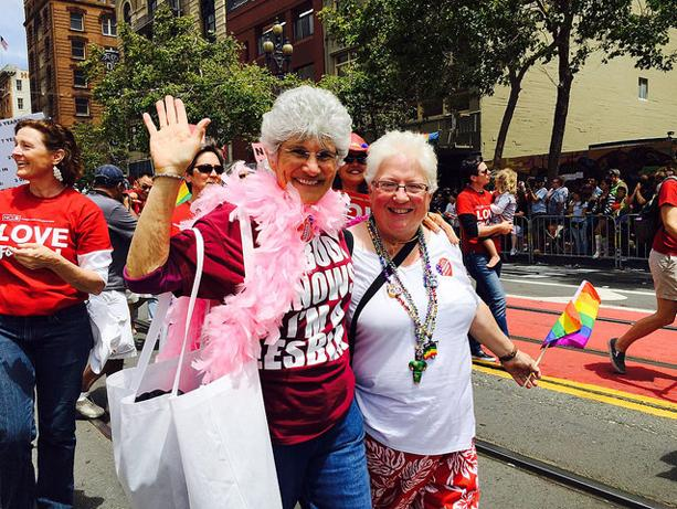 Two women walk in the 2015 Pride Parade in San Francisco.