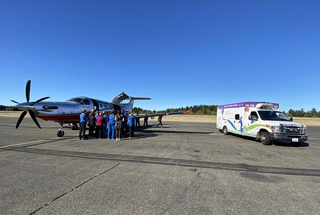 picture of a group beside an Airlift Northwest turboprop plane