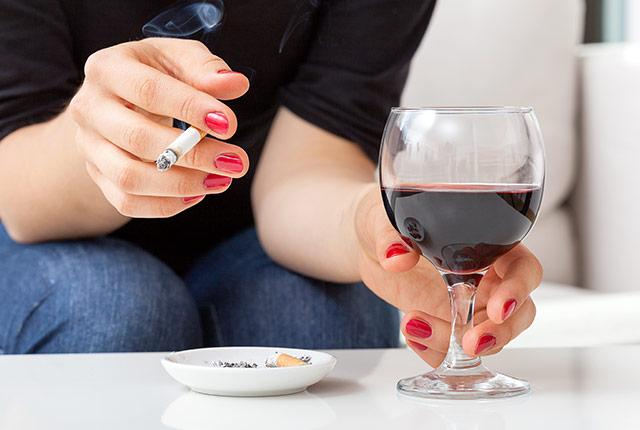 picture of woman's hands holding cigarette and glass of wine
