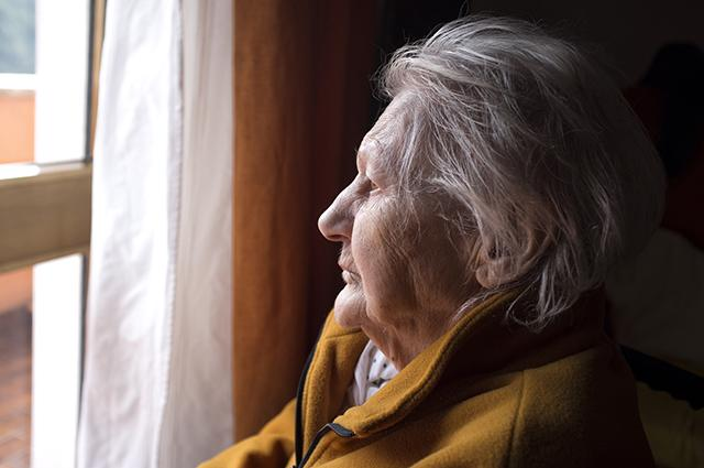 Older woman looking through a window