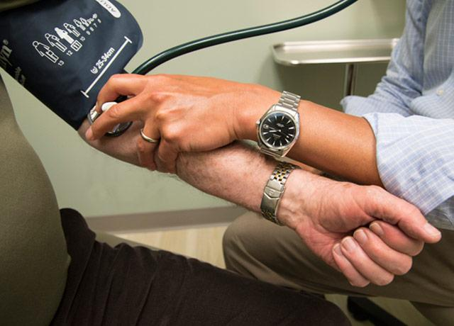 picture of doctor taking blood pressure of patient