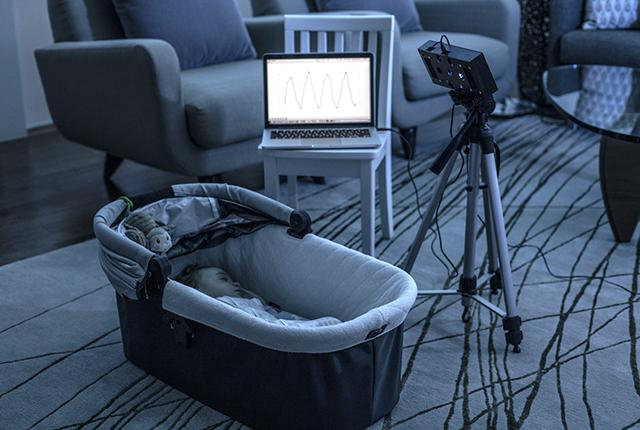 picture of sleeping baby in bassinet beside sound-monitoring equipment