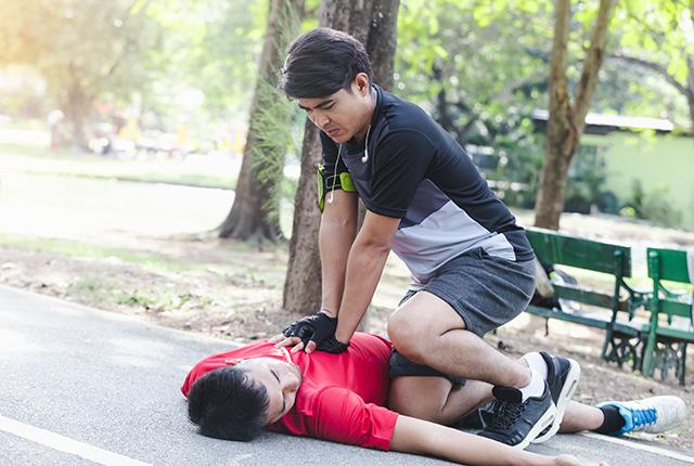 picture of man giving CPR to another man who has fallen to the ground