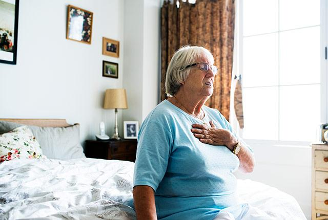 picture of older woman experiencing chest pain on a bed