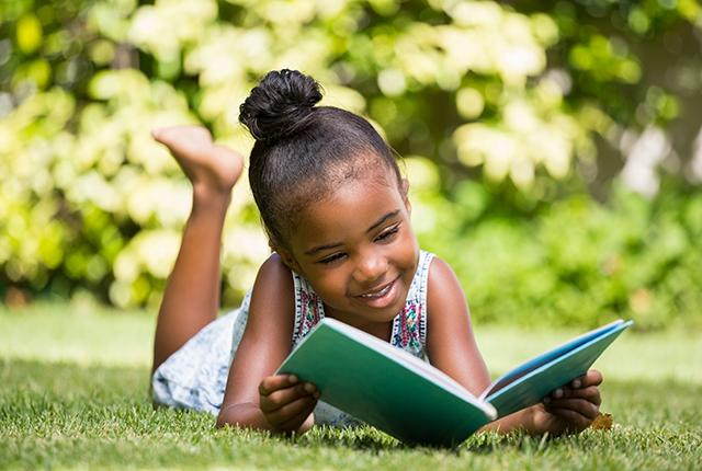 picture of a young girl of color reading outside