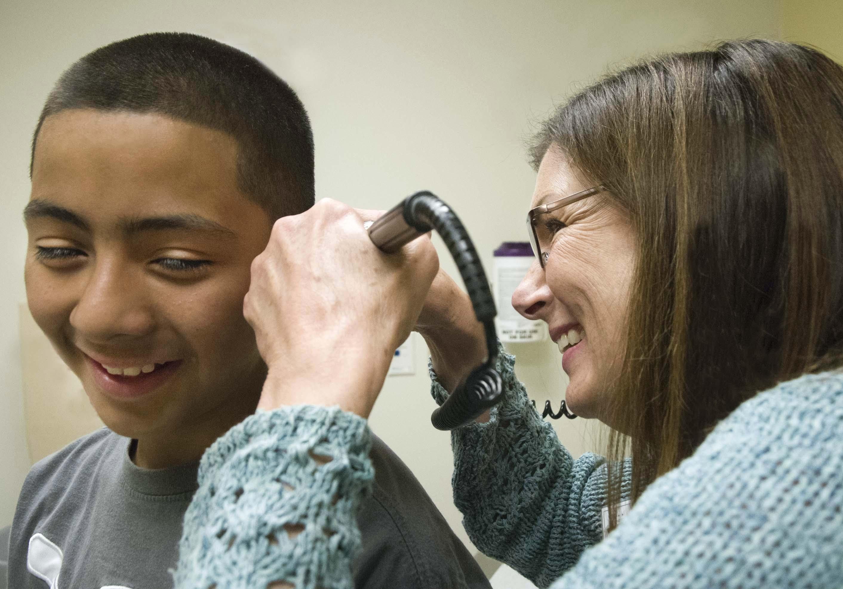 Pediatric nurse practitioner Barb Moravec with young male patient at the Pediatrics Clinic at Harborview. Medical Center