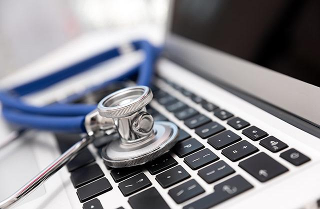 picture of stethoscope sitting on laptop computer