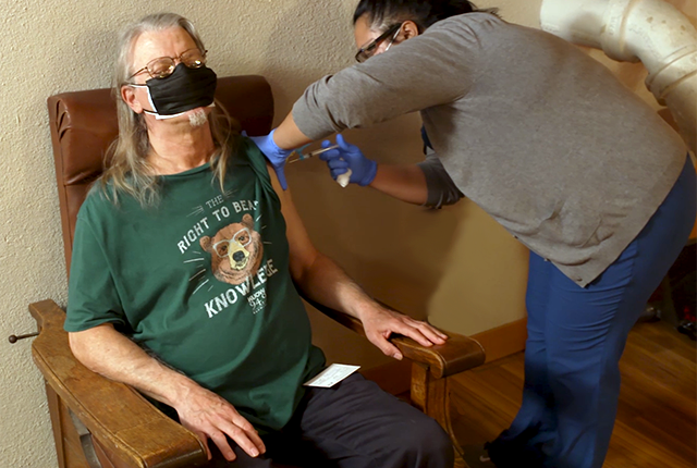 A UW Medicine nurse vaccinates a man against COVID-19 at pop-up clinic in a Seattle low-income housing facility.