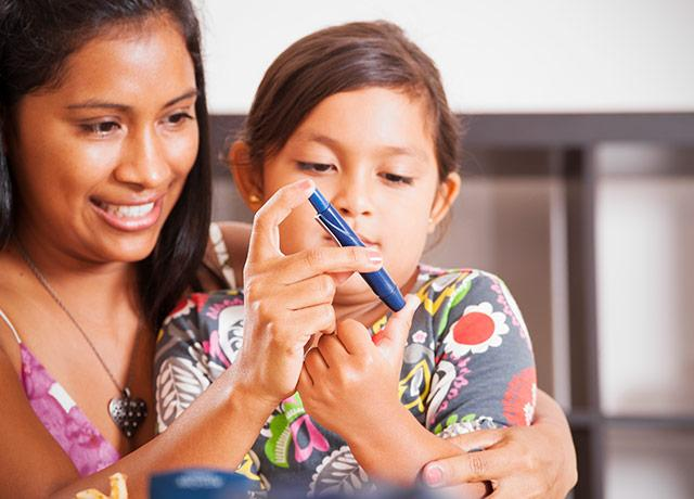 picture of a parent helping a child monitor her blood sugar level