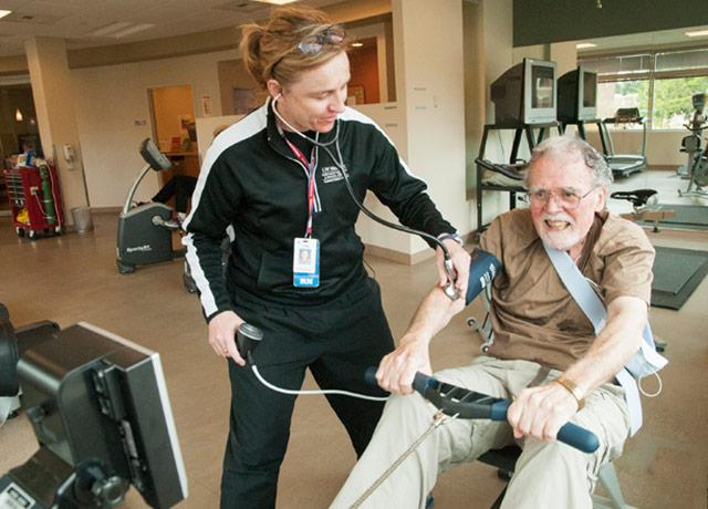 picture of nurse monitoring a patient on a rowing machine during cardiac rehab session