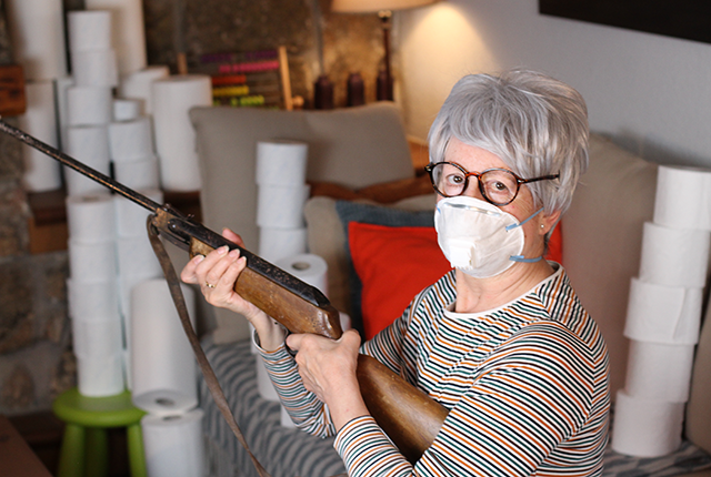 picture of older woman wielding a rifle inside a home
