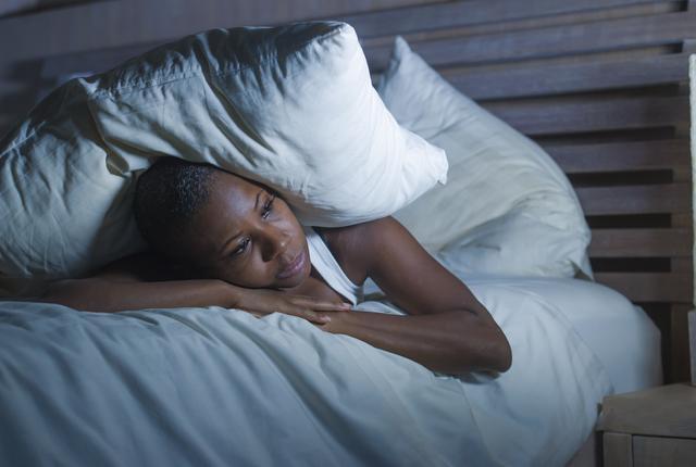 woman lying in bed, awake at night
