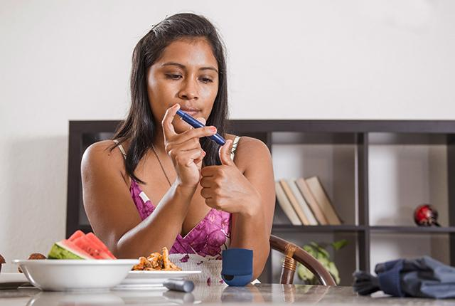 picture of a Latino woman testing her blood sugar