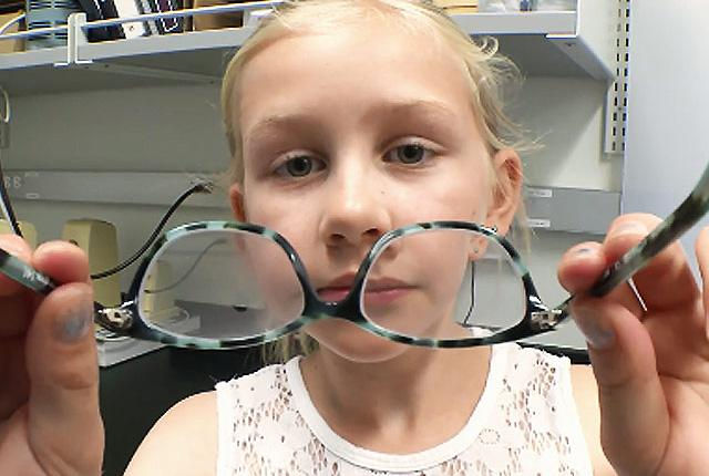 picture of girl holding eyeglasses