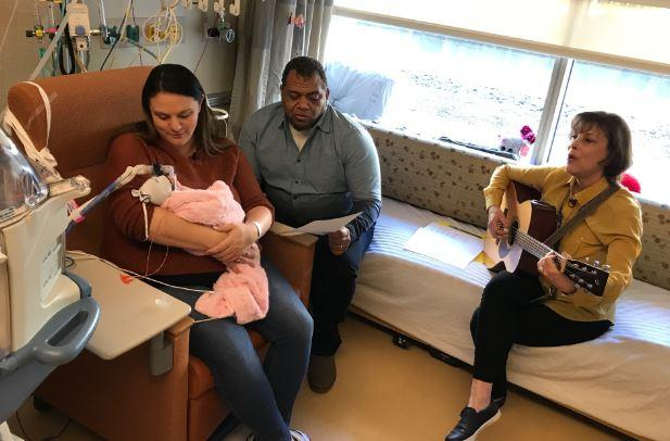 picture of a couple singing to their newborn in the NICU