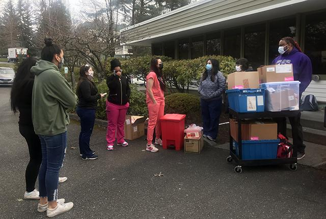 Harborview staffers huddle before giving COVID-19 vaccinations in Federal Way, Washington