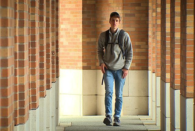 Charlie Yanny walking down a hall.