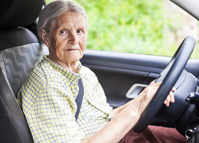 a senior citizen sitting behind the wheel of a car
