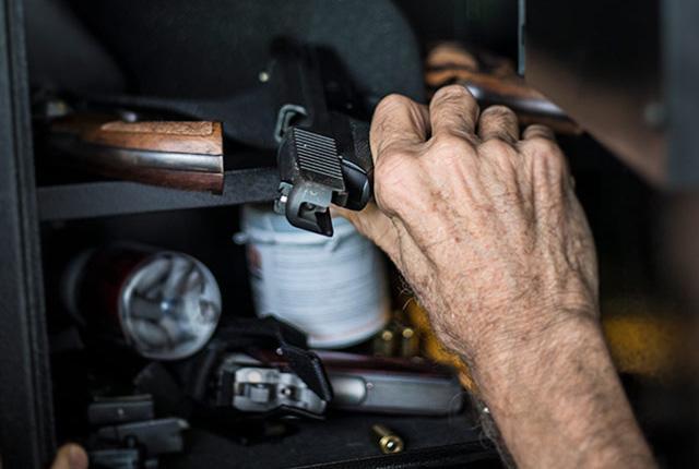 a hand reaches for a firearm in a gun safe