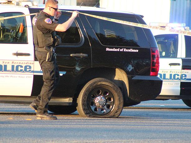 picture of a San Bernadino, California, police officer lifting a crime-scene tape