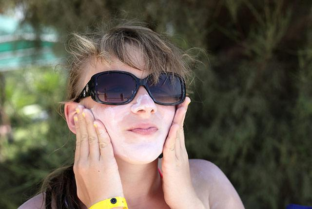 a young woman applies sunscreen to her face