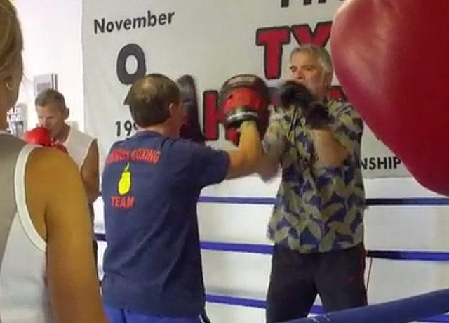 Bret Summers, left, coaches a Parkinson's patient at his gym.