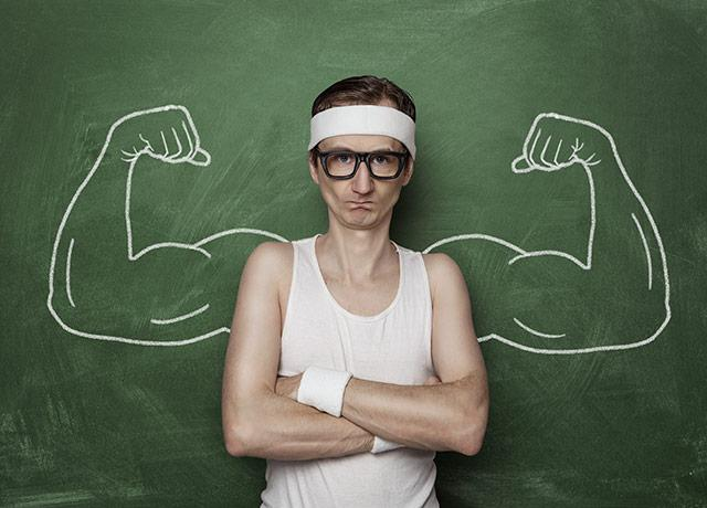 skinny man in front of muscled arms drawn on blackboard