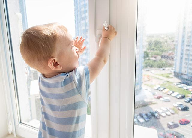 picture of a toddler trying to open an upper-story window