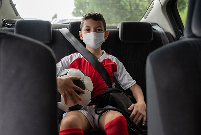 boy in back of car going to soccer game, with mask