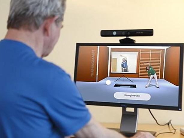 a man watches an online illustration of exercise on a desktop monitor