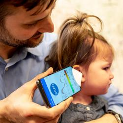 picture of Dr. Randall Bly, an assistant professor of otolaryngology-head and neck surgery at the UW School of Medicine who practices at Seattle Children's Hospital, uses the app and funnel to check his daughter's ear.