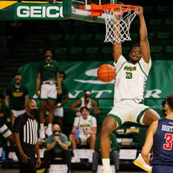 picture of college basketball player dunking during a game in 2021