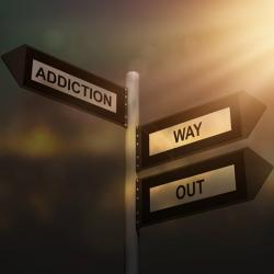 Directional signs saying addiction and way out