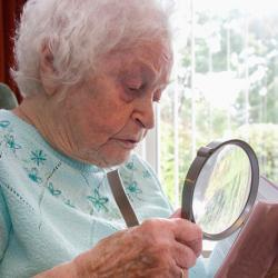 elderly woman reading with a magnifying glass