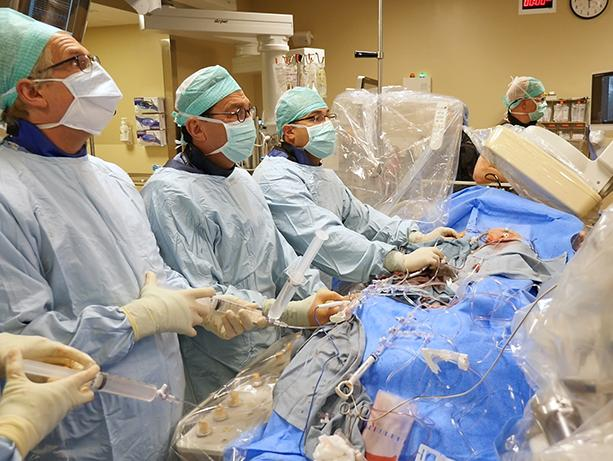 picture of UW Medicine cardiologist Danny Dvir leading a team of UW Medicine heart specialists in performing a never-before-tried technique to replace a patient's failed artificial aortic valve.