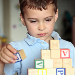 Child with autism deciding where is the best place to put his block.