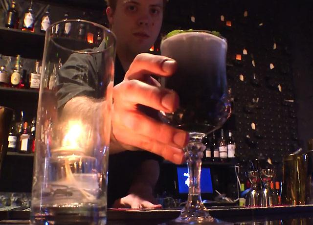 picture of bartender placing drink that is part charcoal
