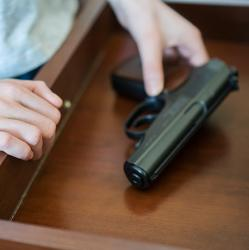 picture of a child picking up a handgun from a drawer
