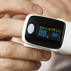 picture of man using a pulse oximeter that shows 88 blood oxygen saturation