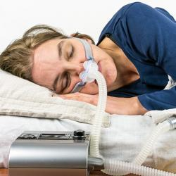 picture of a woman wearing a CPAP in bed