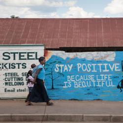 Woman and children walking in Zambia by colorful sign saying Stay Positive. Life is Beautiful.