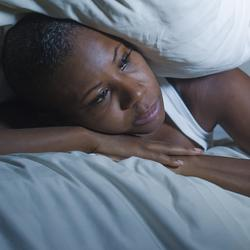 woman lying in bed, awake at night