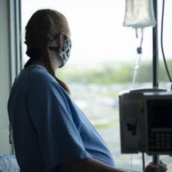 woman looking out the window of hospital