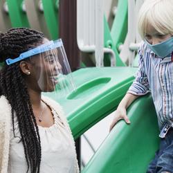 woman watching children play on slide set