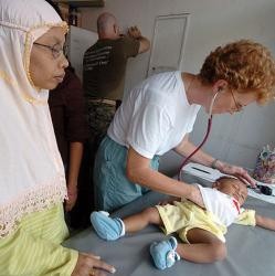 picture of Navy nurse examining child at hospital in Indonesia