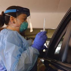 photo of a UW Medicine nurse preparing to screen a patient at a drive-through clinic