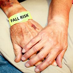 "picture of two seniors hands touching; one has a bracelet that reads ""Fall Risk"""