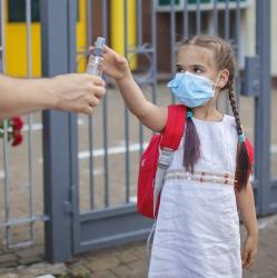 kid going to school in a mask and getting hand sanitizer